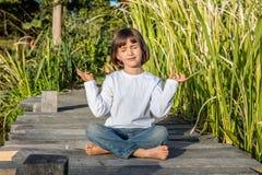 做松弛能量的微笑的漂亮的孩子瑜伽赤脚 免版税库存图片