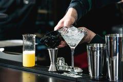 做松弛鸡尾酒的侍酒者在酒吧背景 免版税库存照片