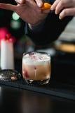 做松弛鸡尾酒的侍酒者在酒吧背景 免版税库存图片