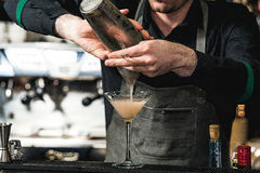 做松弛coctail的侍酒者在酒吧背景 免版税库存图片