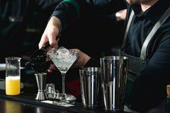 做松弛coctail的侍酒者在酒吧背景 库存图片