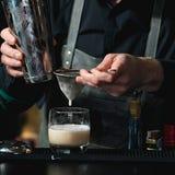 做松弛coctail的侍酒者在酒吧背景 库存照片