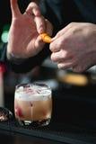 做松弛coctail的侍酒者在酒吧背景 免版税库存照片