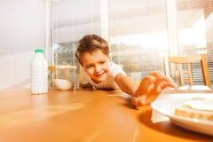 做板材的逗人喜爱的男孩一条长的胳膊用三明治 免版税库存图片
