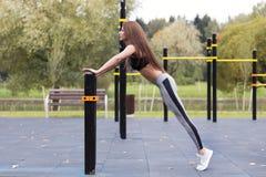 做板条或俯卧撑锻炼的适合的女孩室外在公园温暖的夏日 耐力和刺激的概念 免版税库存图片
