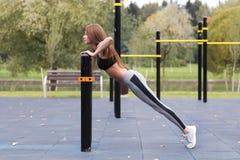 做板条或俯卧撑锻炼的适合的女孩室外在公园温暖的夏日 耐力和刺激的概念 免版税库存照片