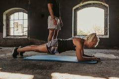 做板条的健身妇女,当站立在她旁边时的教练员 库存图片