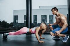 做板条锻炼训练和有教练员的嬉戏妇女新闻肌肉 体育健身锻炼力量力量 免版税库存图片