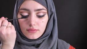 做构成的女性手画象使用可爱的回教妇女的染睫毛油在黑背景的hijab的 股票录像