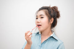 做构成的美丽的亚裔少妇使用嘴唇 库存图片