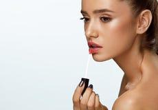 做构成的美丽的妇女使用在嘴唇的嘴唇光泽 化妆用品 图库摄影