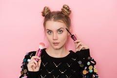 做构成的美丽的年轻妇女使用染睫毛油和粉末刷子 免版税图库摄影