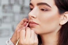 做构成的过程 化妆师与在式样面孔的刷子一起使用 年轻女人画象美容院内部的 库存照片