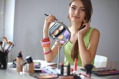 做构成的年轻美丽的妇女在镜子附近 免版税库存图片