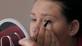 做构成,在眼睛,眼线膏的凹道箭头的美丽的女孩特写镜头 影视素材