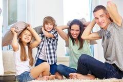 做枕头战的家庭和孩子 免版税库存照片