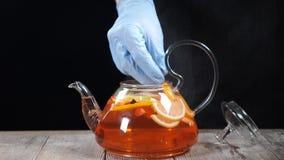 做果子茶 放切片桔子的侍酒者入用不同的果子的煮沸的茶壶在它 慢的行动 股票视频