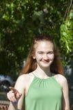 做枪射击姿态的快乐的女孩 偶然享用的悠闲时间的美丽的年轻女人在城市公园,转动的回合,微笑 图库摄影