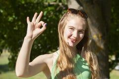 做枪射击姿态的快乐的女孩 偶然享用的悠闲时间的美丽的年轻女人在城市公园,转动的回合,微笑 库存图片