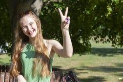 做枪射击姿态的快乐的女孩 偶然享用的悠闲时间的美丽的年轻女人在城市公园,转动的回合,微笑 免版税图库摄影