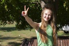 做枪射击姿态的快乐的女孩 偶然享用的悠闲时间的美丽的年轻女人在城市公园,转动的回合,微笑 免版税库存照片