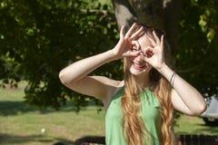 做枪射击姿态的快乐的女孩 偶然享用的悠闲时间的美丽的年轻女人在城市公园,转动的回合,微笑 库存照片