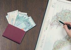 做标志的一只女性手在马来西亚的地图计划的一次新的旅行 旅行护照和马来西亚人金钱在背景 免版税库存照片