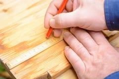 做标记的工匠在与一支红色笔的木头 免版税库存照片