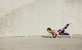 做核心锻炼的年轻肌肉妇女 免版税库存图片