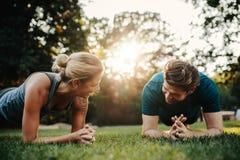 做核心锻炼的白种人夫妇在公园 免版税库存图片