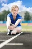 做核心锻炼的美丽的妇女在体育场 免版税库存图片
