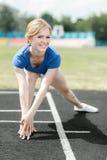 做核心锻炼的美丽的妇女在体育场 免版税库存照片