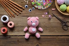 做桃红色猪 钩编编织物孩子的玩具 在桌上穿线,针,勾子,棉纱品 第1步-编织玩具所有细节  免版税库存图片
