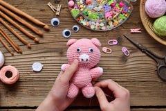 做桃红色猪 钩编编织物孩子的玩具 在桌上穿线,针,勾子,棉纱品 第2步-缝合玩具所有细节  手工制造 库存图片