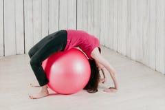 做桥梁的女孩摆在健身房的一桃红色fitball 免版税库存照片