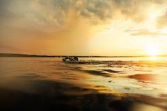做横跨湖的运动人游泳在日落 库存照片