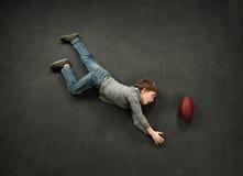 做橄榄球的男孩鱼跃接球 库存照片