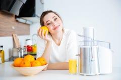 做橙汁的可爱的妇女在厨房 图库摄影