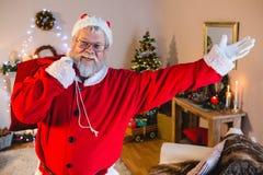 做欢迎姿态的圣诞老人,当运载他的礼物大袋时 库存照片