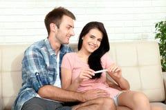 做正面妊娠试验和庆祝的愉快的激动的夫妇 库存图片