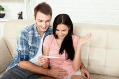 做正面妊娠试验和庆祝的愉快的激动的夫妇 免版税库存图片