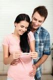 做正面妊娠试验和庆祝的愉快的激动的夫妇 免版税图库摄影