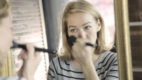 做每天构成和拿着在镜子前面的美丽的妇女构成刷子 影视素材