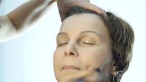 做每天构成的专业化妆师特写镜头,在与刷子的妇女面颊上把粉末放 股票录像