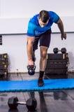 做水壶响铃锻炼的适合的年轻人在健身房 图库摄影