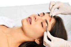 做永久眼眉构成的美容师 特写镜头结构的与厚实的眉头的美丽的妇女面孔在美容院 库存图片