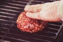 做汉堡包小馅饼的厨师在厨房里用绞细牛肉 免版税库存图片