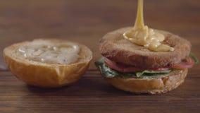 做汉堡特写镜头的厨师的手 厨师倾倒在炸肉排之上的可口调味汁 鲜美食物配制 股票视频