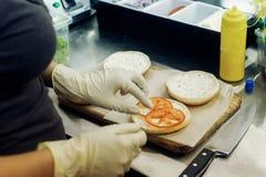 做汉堡的过程 在烹调汉堡包的手套的厨师手 免版税图库摄影