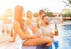 做池边聚会在日落-年轻人的小组愉快的朋友笑和饮用乐趣饮用的香槟在假期 库存图片